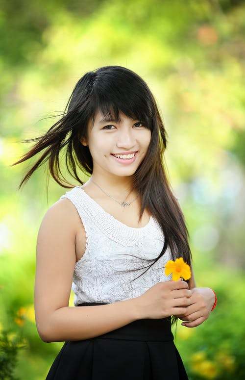Woman Wearing White and Black Sleeveless Dress Holding Yellow Flower Selective-focus Photography