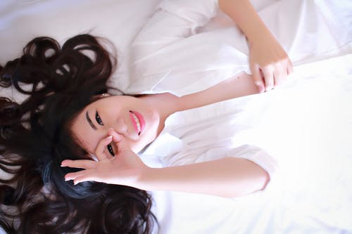 Smiling Woman Lying on White Bed