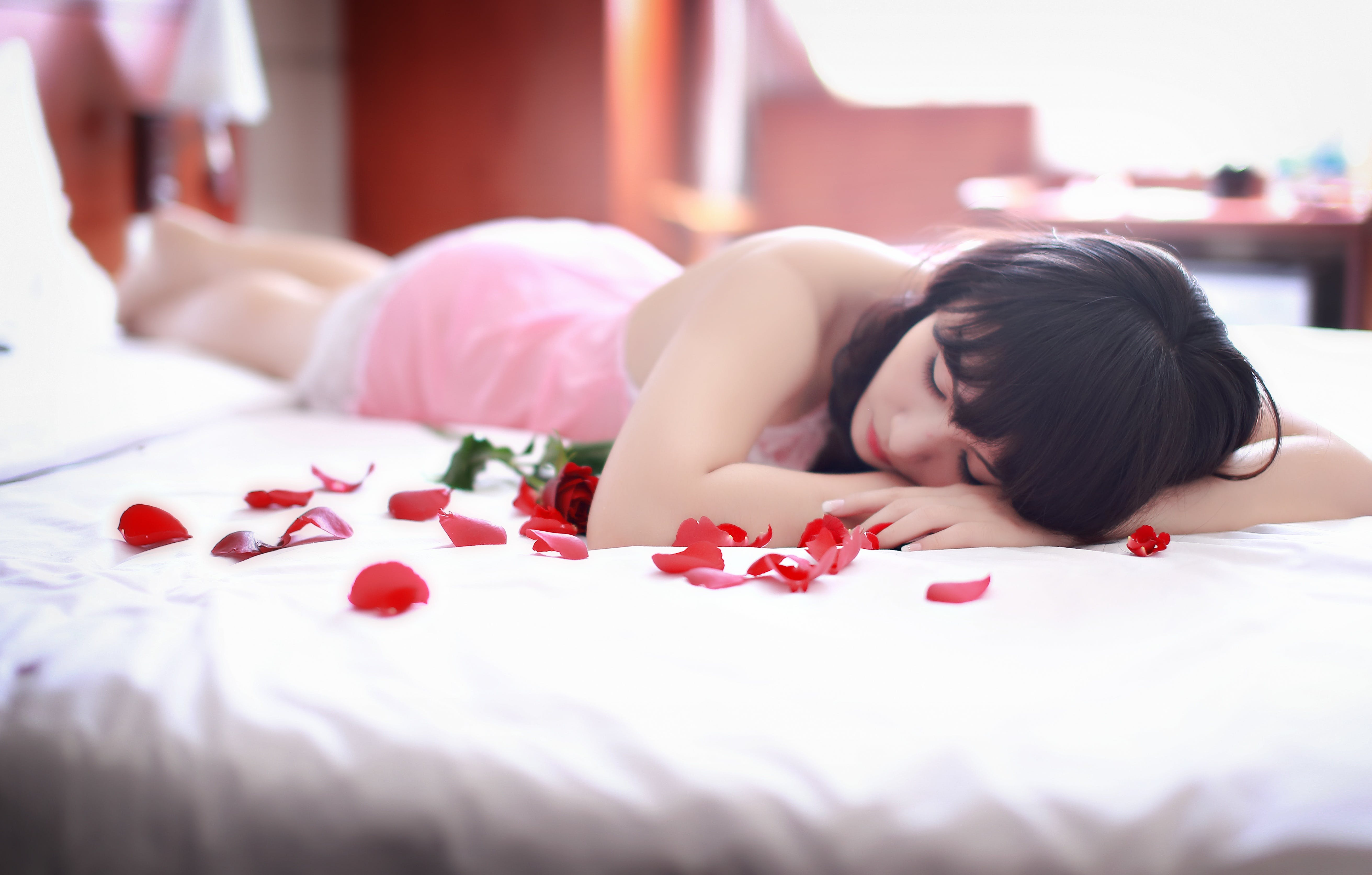 Woman Lying on White Bed With Roses