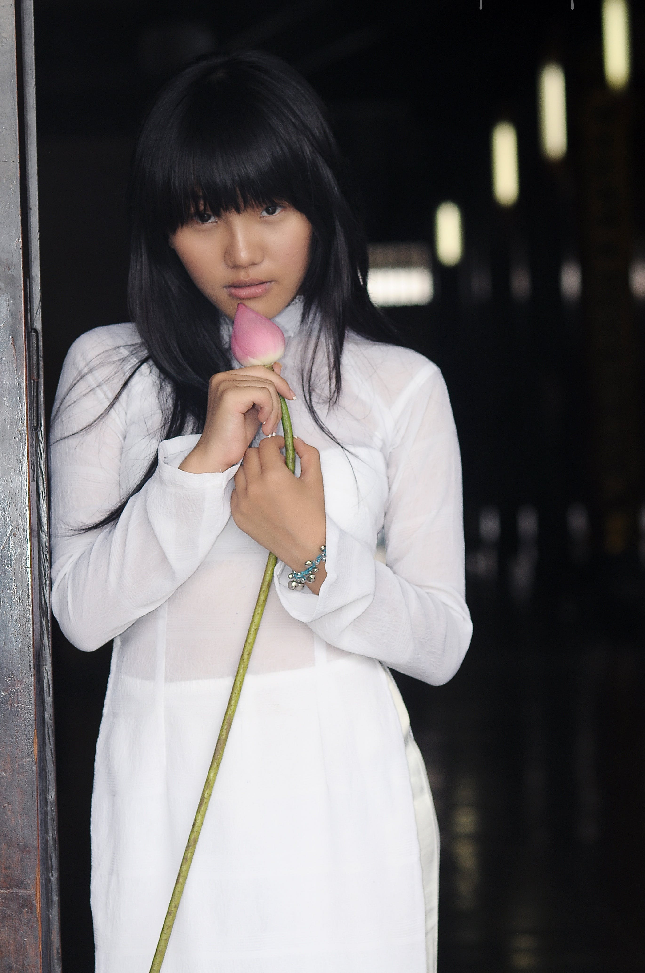 Woman Wearing White Long-sleeved Dress Holding a Pink Lotus Flower Bud Leaning on Grey Wall