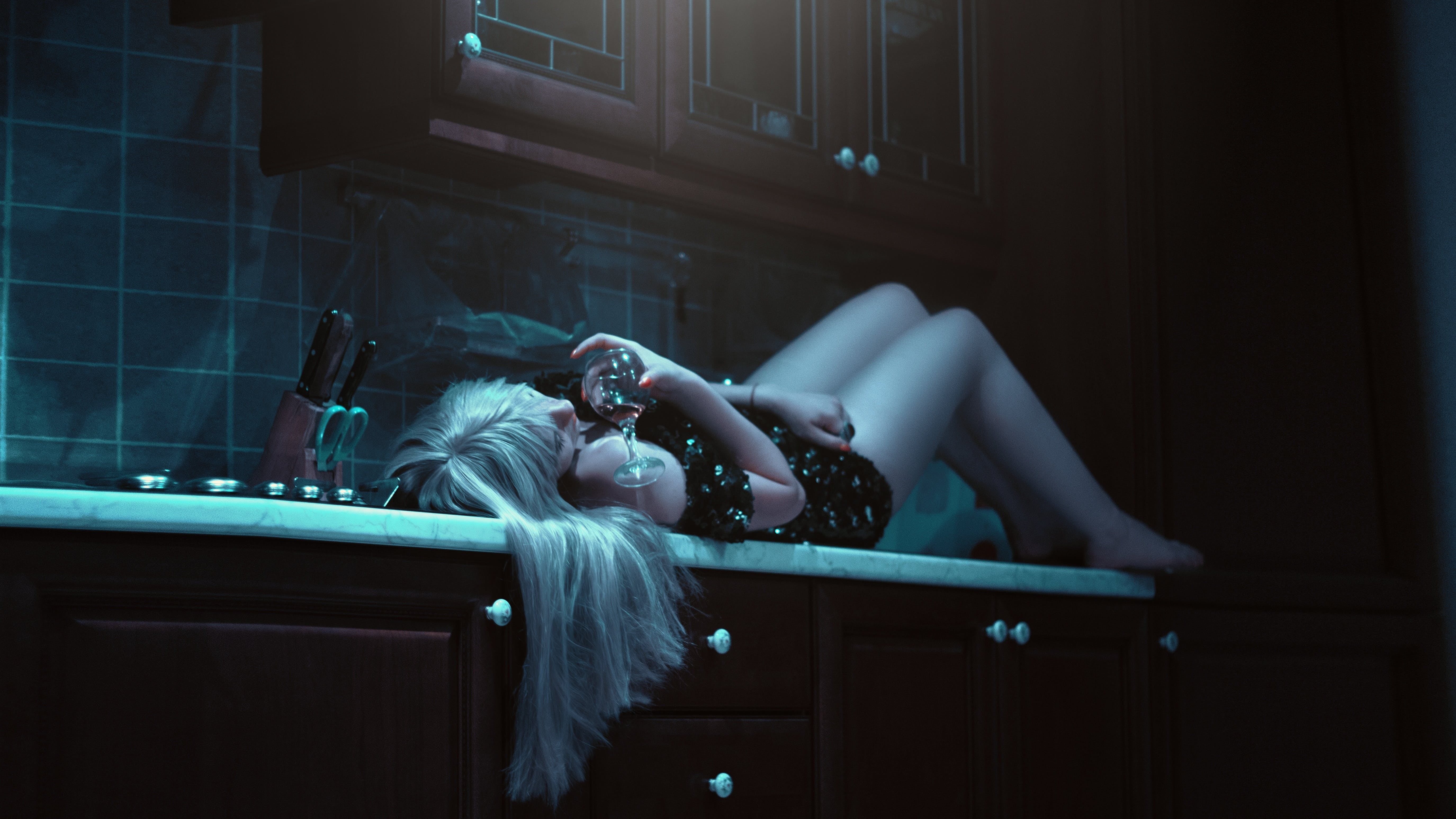 Woman Lying on Kitchen Cabinet Holding Wine Glass