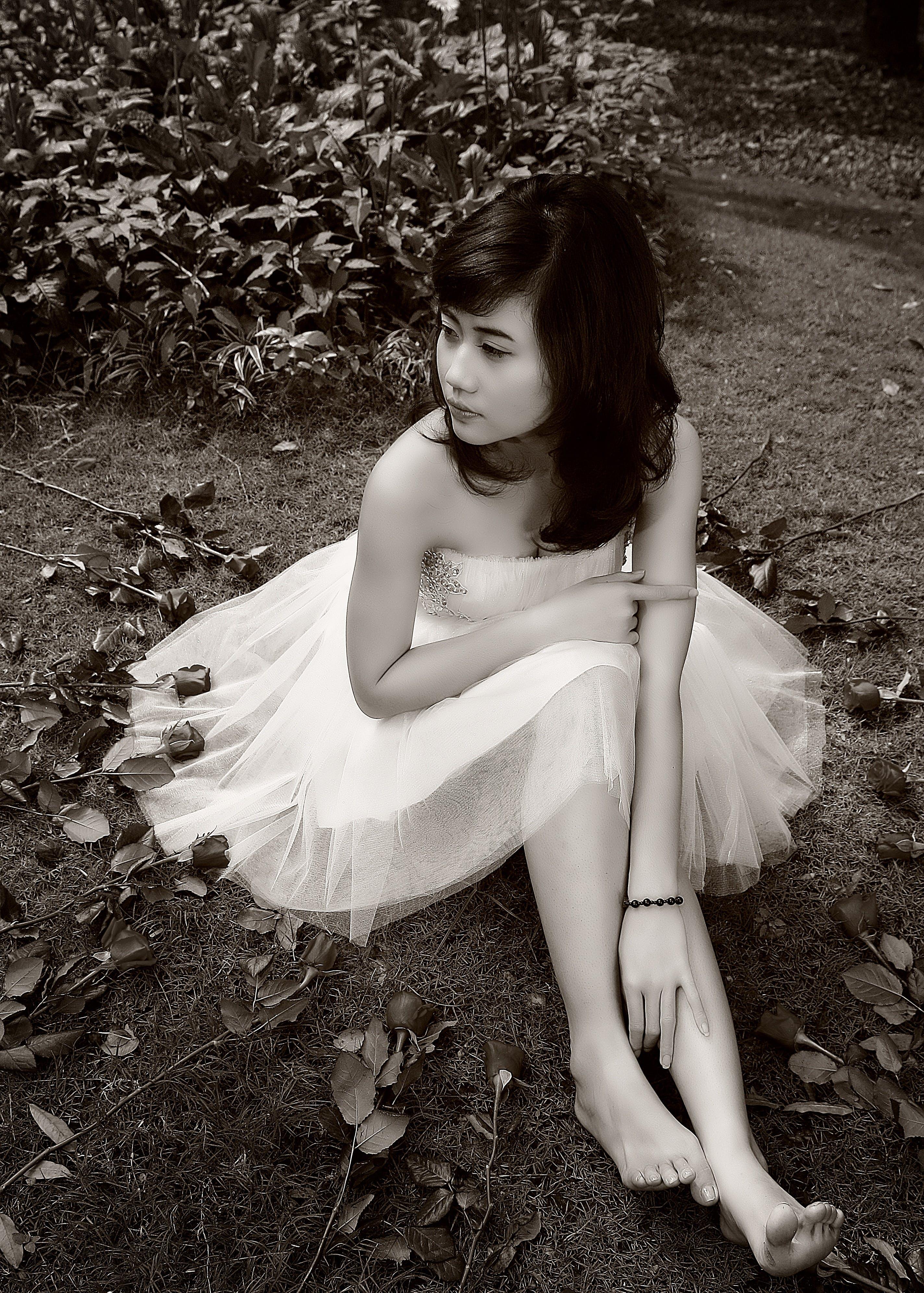 Woman Sitting on Ground Near Plants