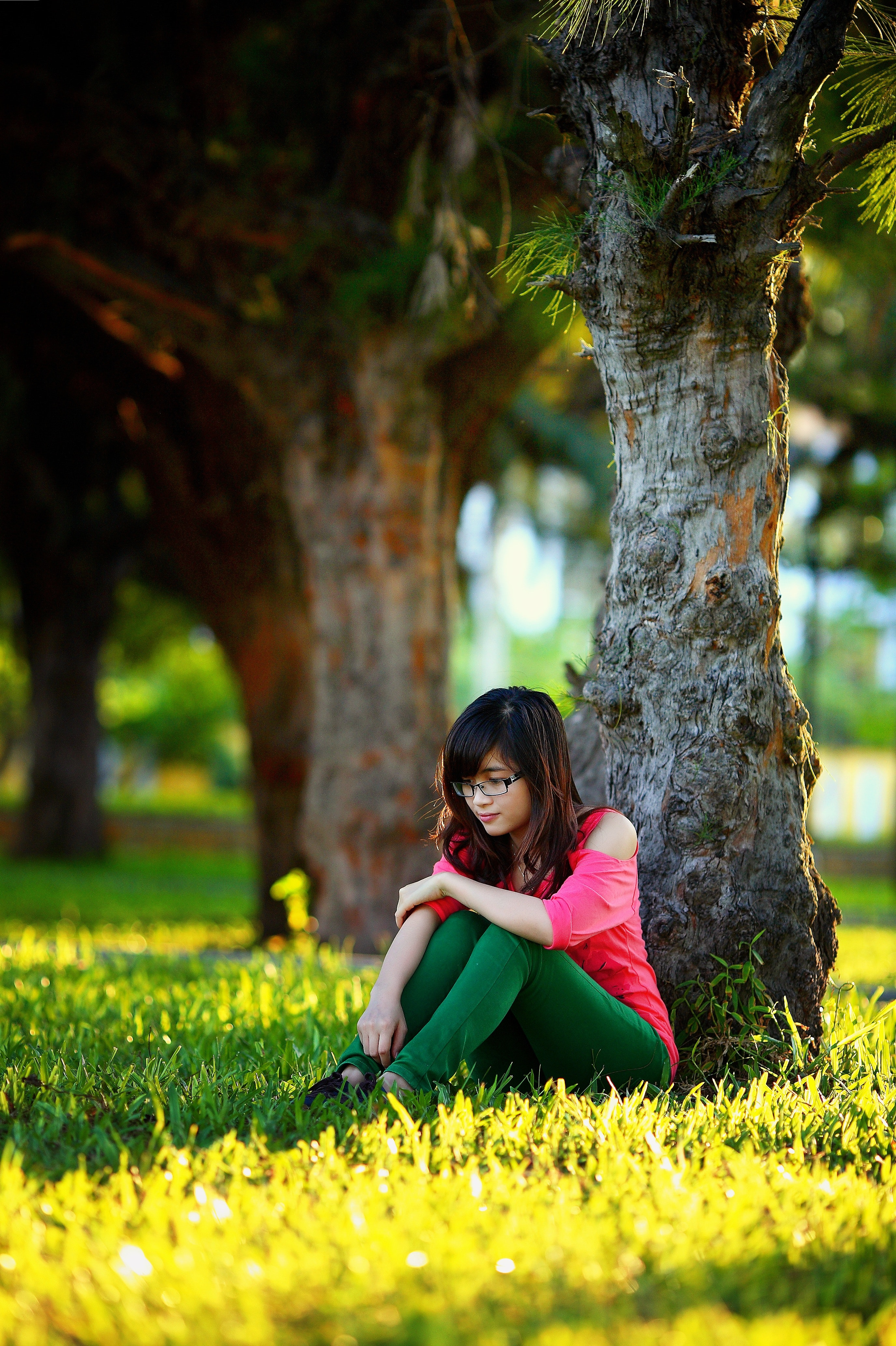 2 Woman Sitting In The Different Bench Chair Near Tree In