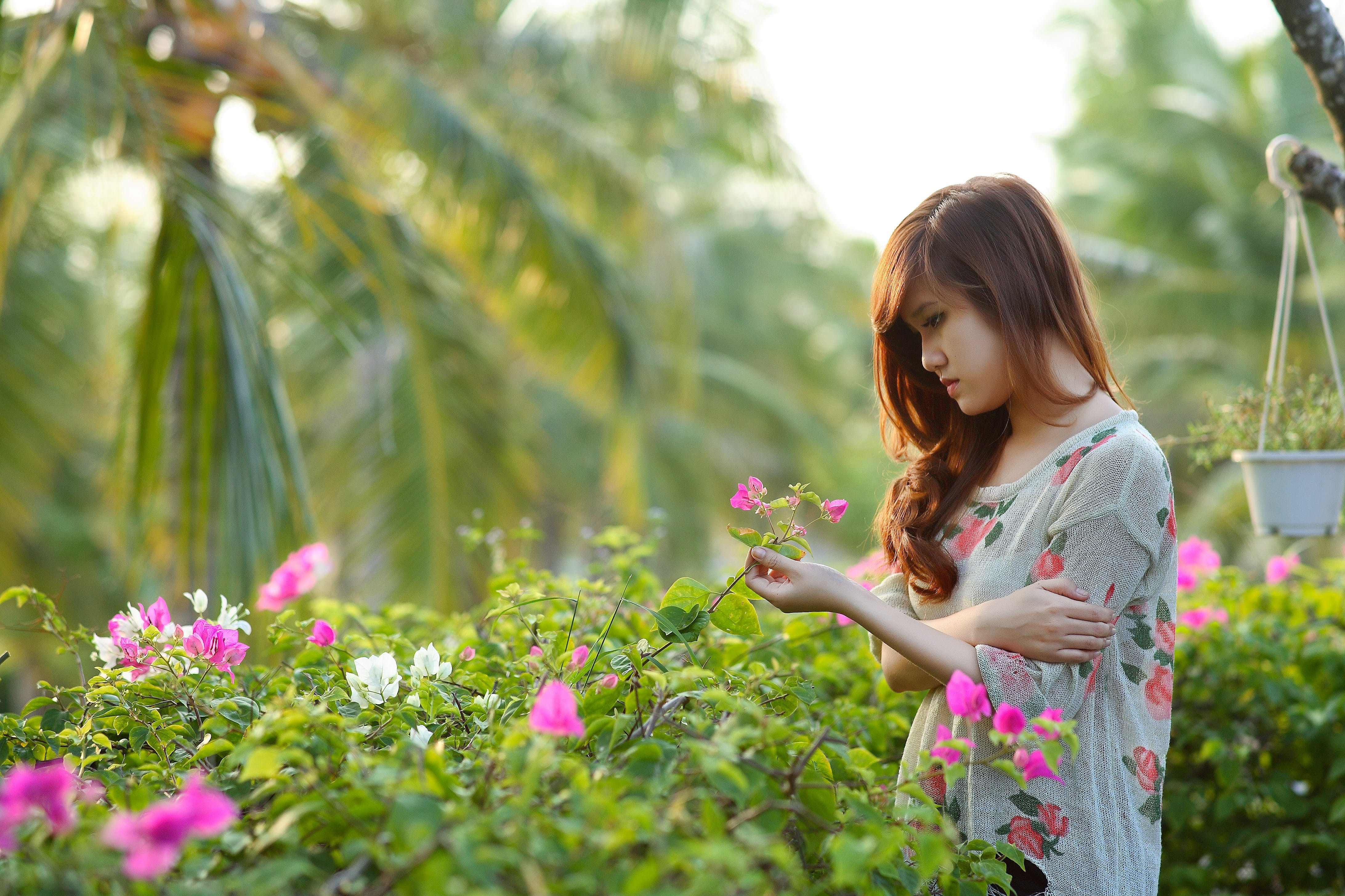 Woman Wearing White, Pink, and Green Floral Dress Holding Pink Bougainvillea Flowers