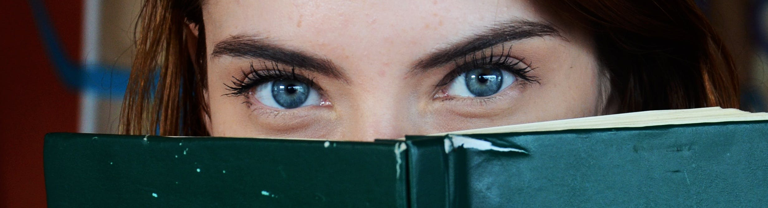 Woman Covering Her Face With Green Book