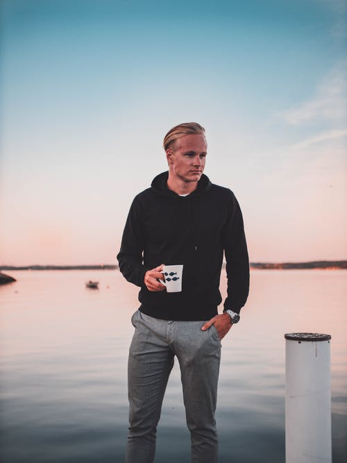 Man Holding Mug While Standing On Dock