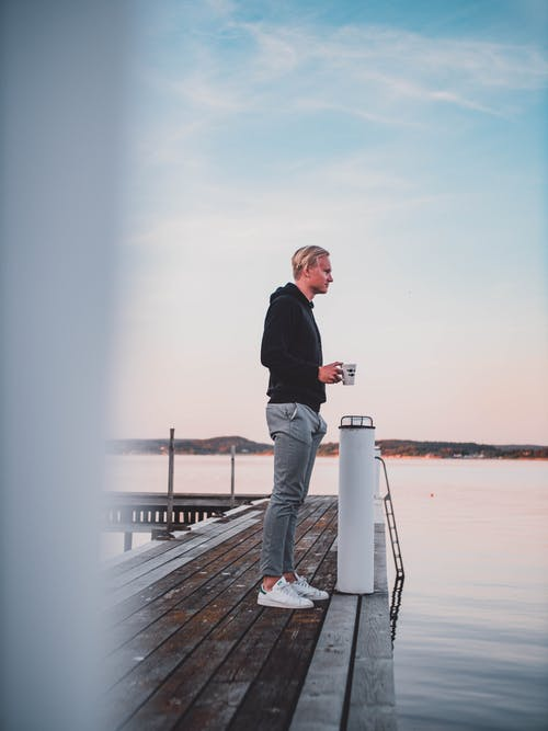 Man Standing On Wooden Dock