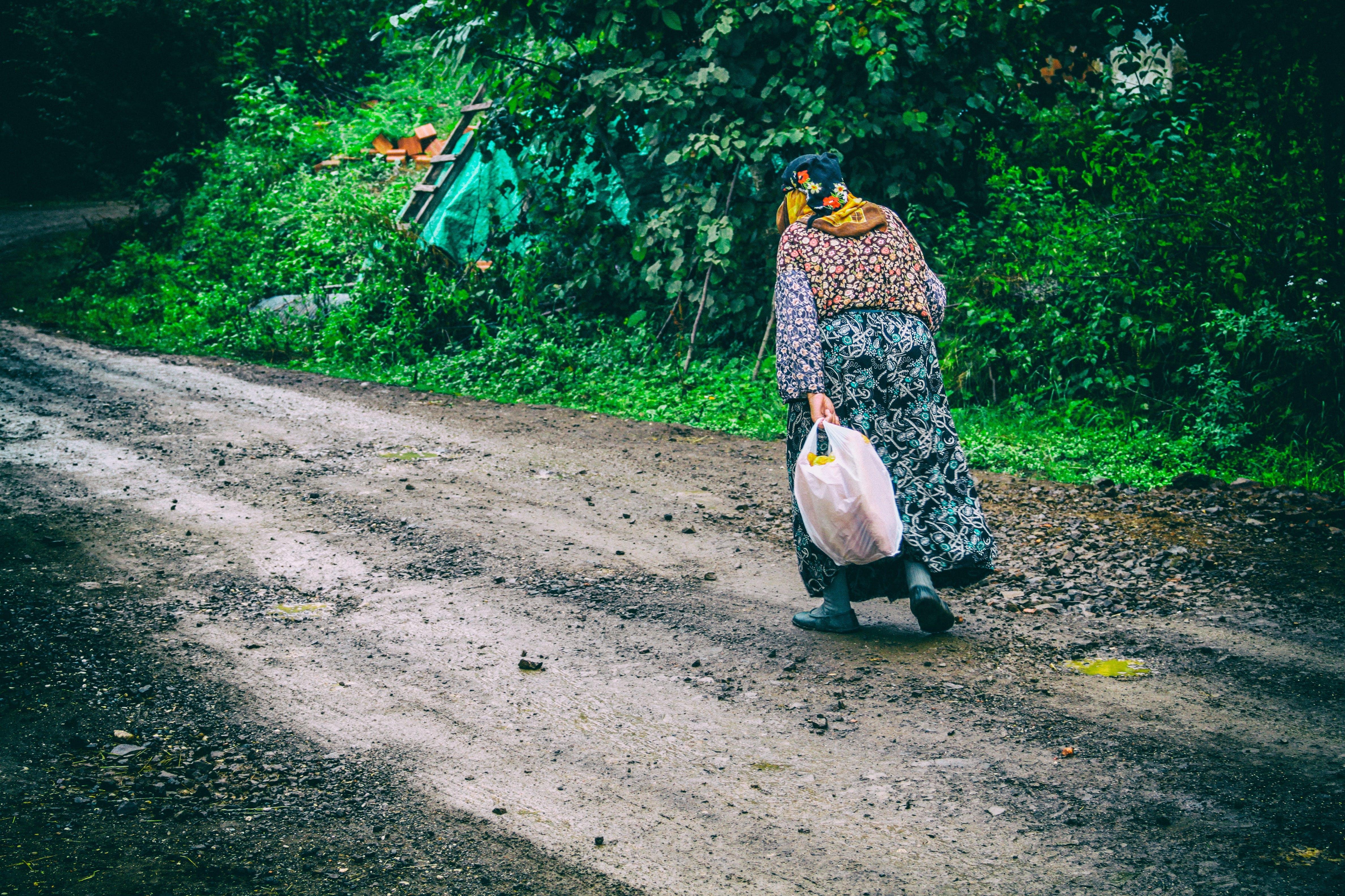 Woman Walks on Brown Soil