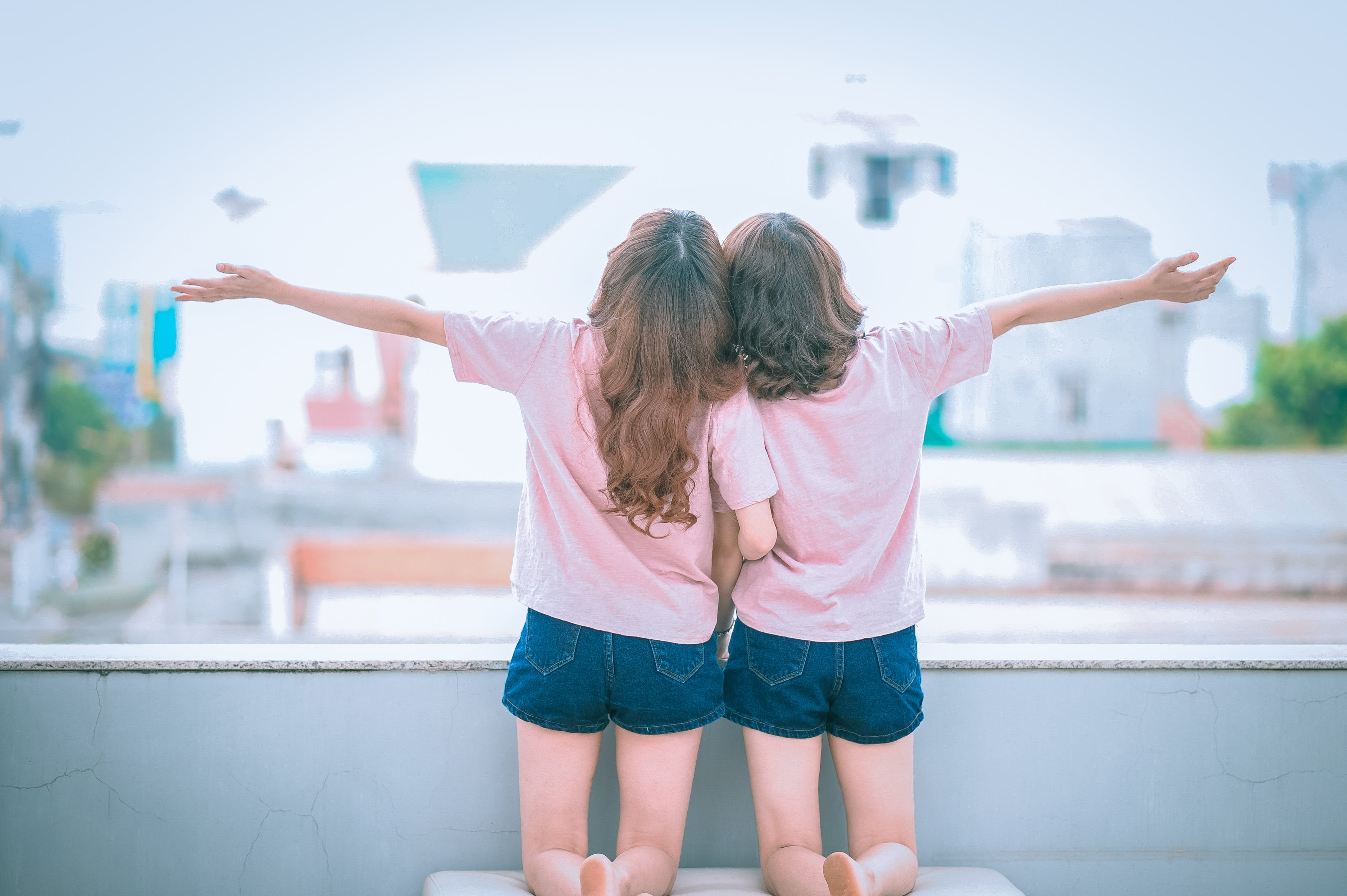Two Girls Spreading Arms Together While Kneeling