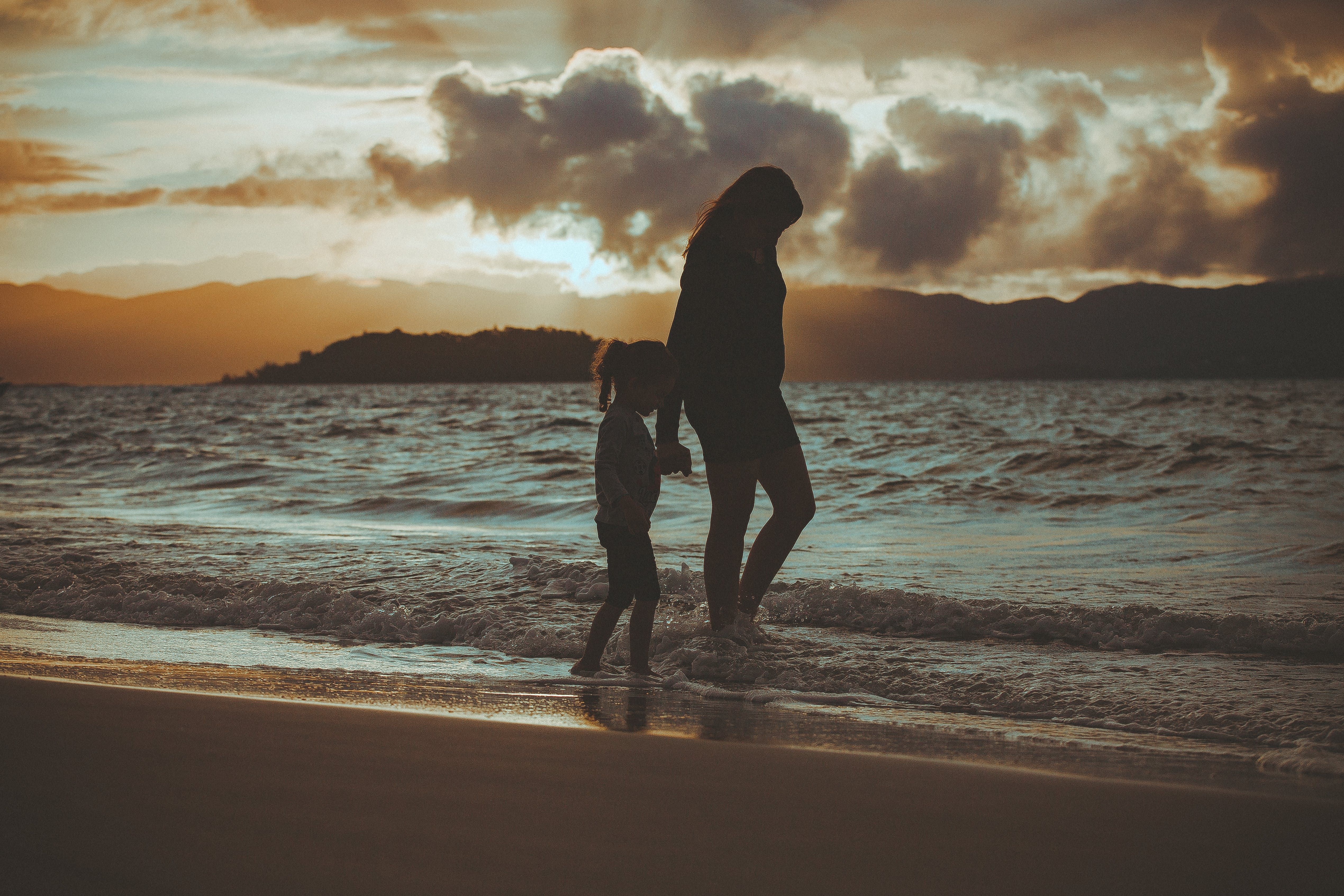 Silhouette Of Woman And Girl Walking On Seashore
