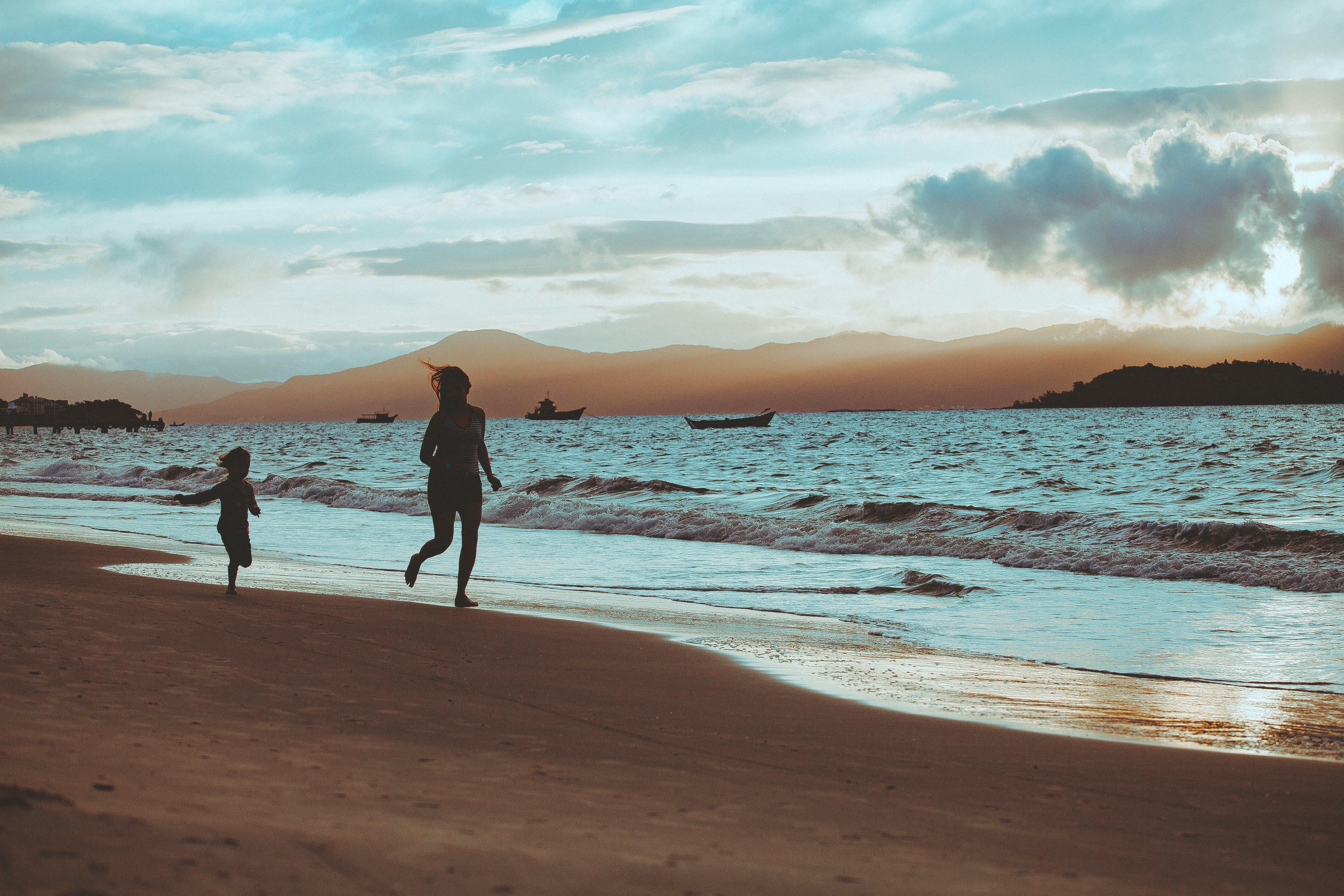 Photo of People Running On Seashore