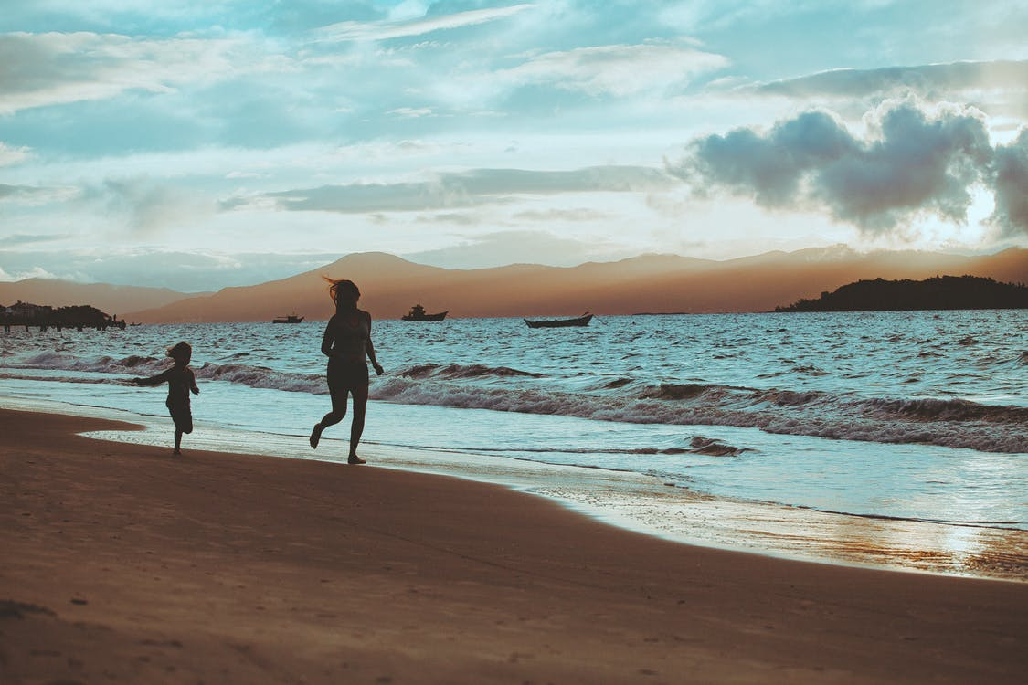 Photo of People Running On Seashore