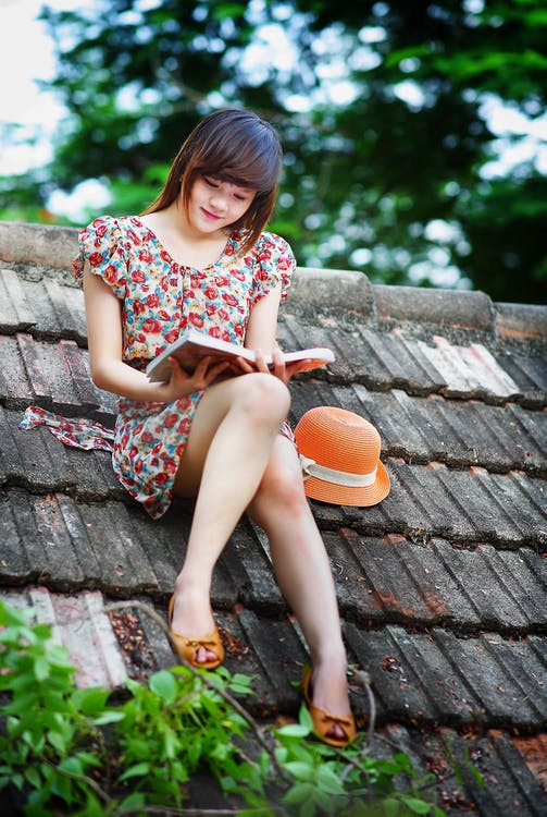 Woman Wearing White, Green, and Red Floral Cap-sleeved Dress Reading a Book on Black Roof Near Green Trees