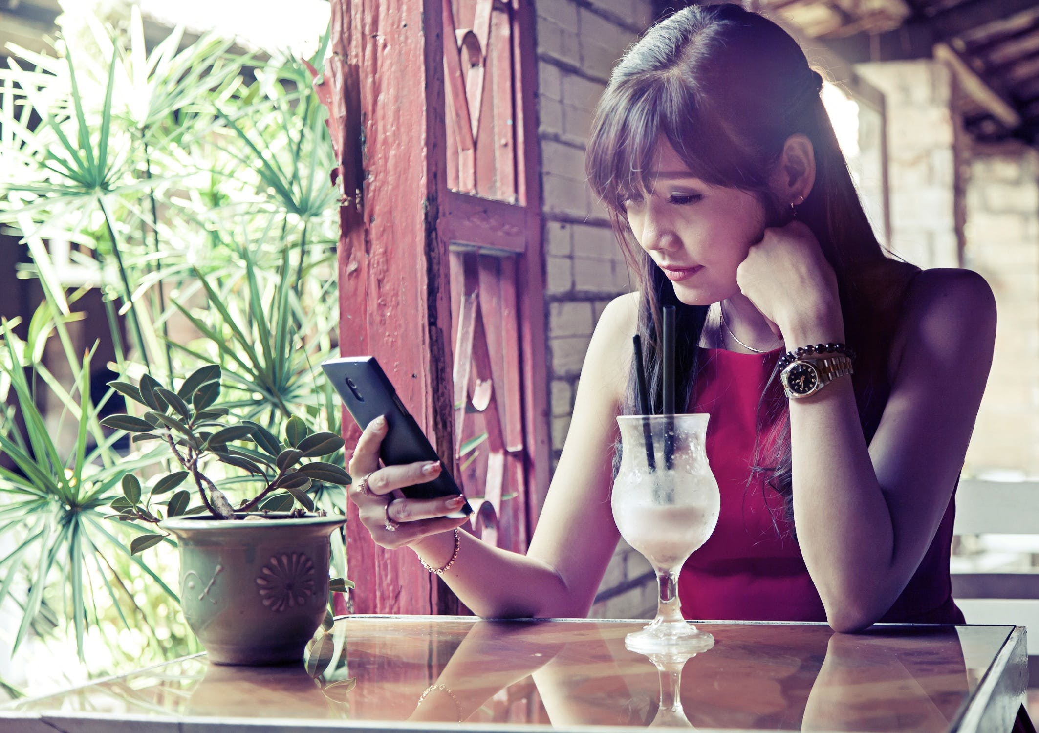 Woman Sitting on Square Brown Table Holding Phone