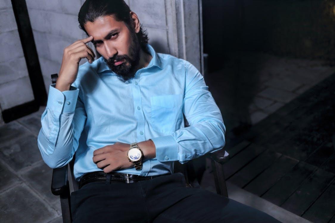 Man Sitting on Black Wooden Armchair Inside Room