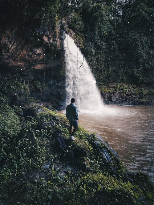 Man Standing Beside Waterfalls