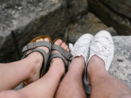 Man and Woman Show Their Feet on Rock
