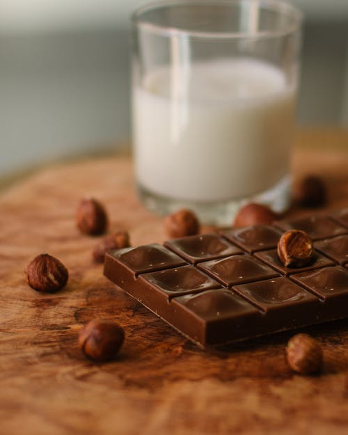 Chocolate Beside Clear Drinking Glass With Milk