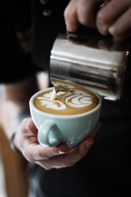 Person Pouring Cream in Espresso