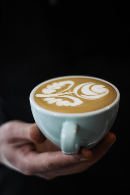 Photo of Hand Holding a Filled Cup Latte