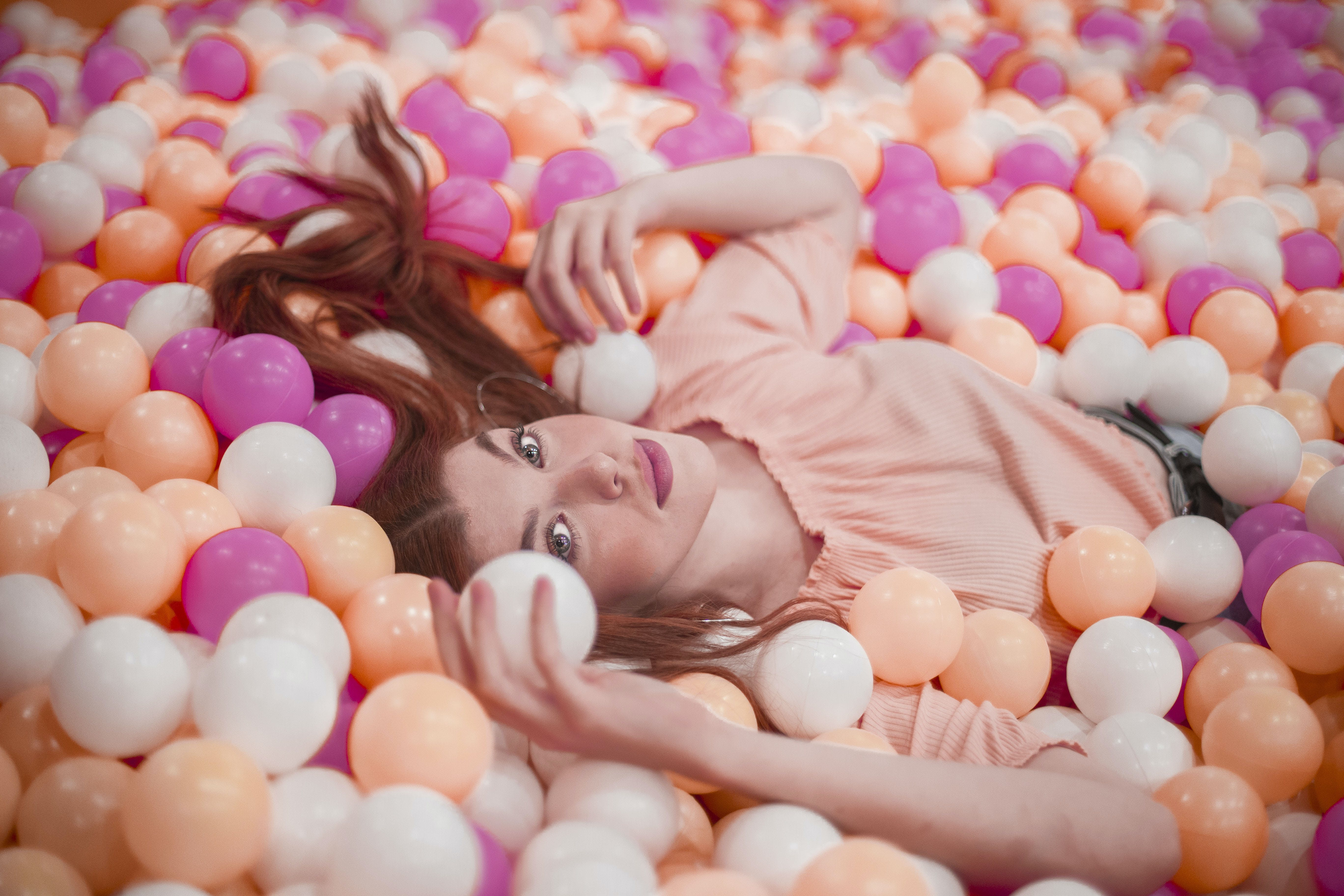 Photo of Woman Lying in Colorful Ball Pool