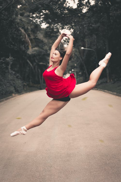 Photo of Ballerina Split Jumping in the Middle of the Road