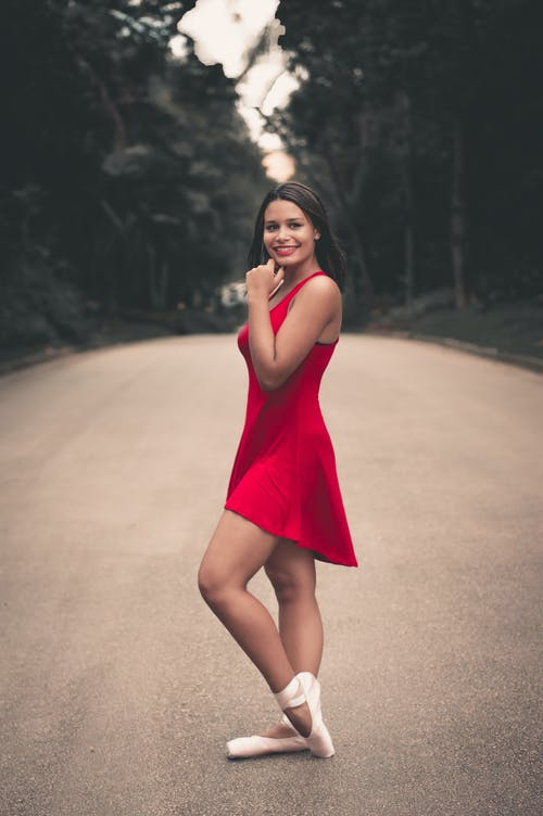 Photo of Ballerina in Red Dress Posing In the Middle of the Road