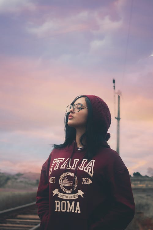 Photo of Woman in Maroon Hoodie and Beanie Hat Standing Next to Train Tracks