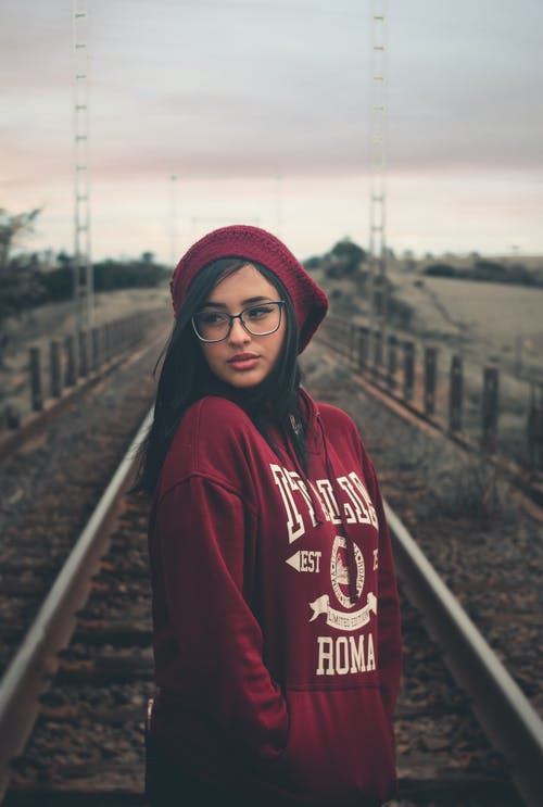 Photo of Woman in Eyeglasses Standing in the Middle of a Train Track