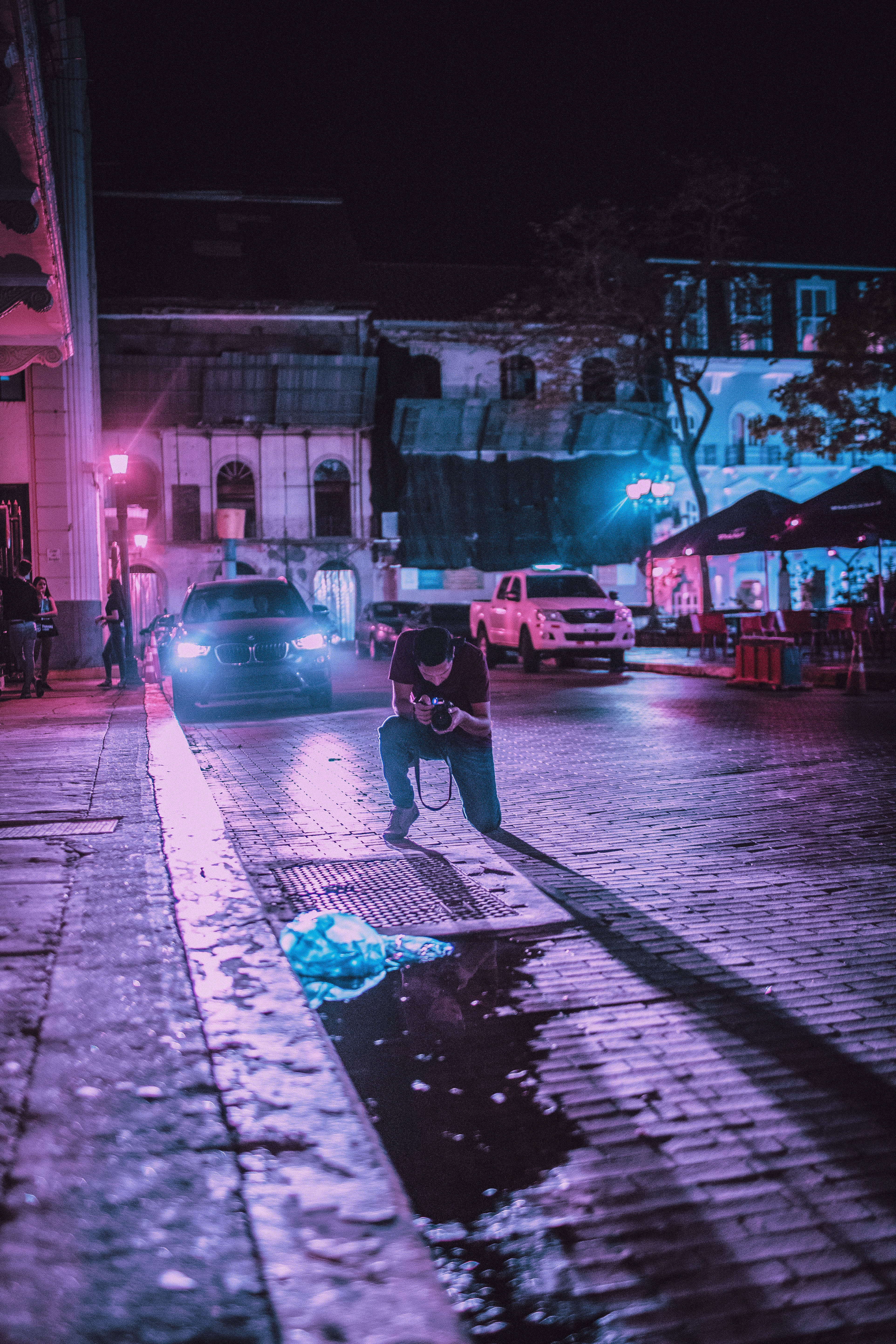 Person Taking Photo of Ground in Front of Vehicle during Night