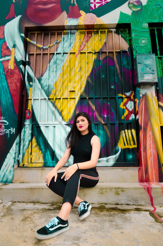 Woman Sitting on Blue and Yellow Graffiti