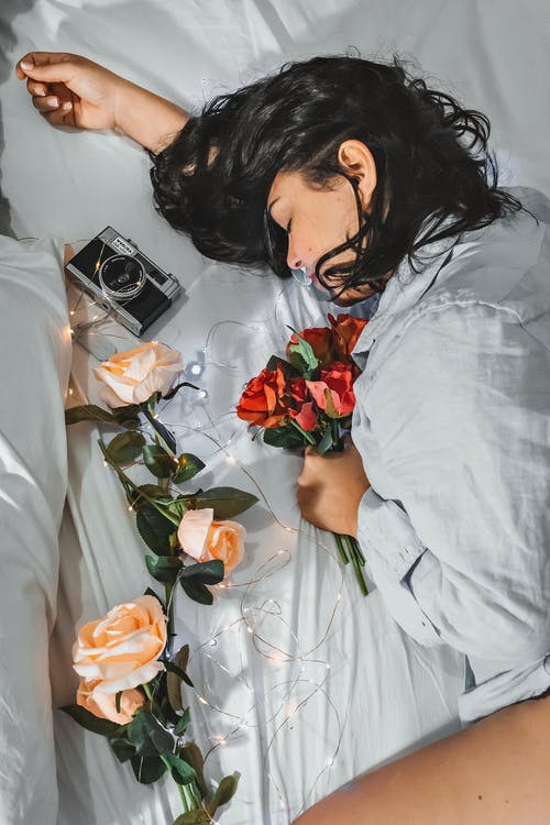 Romantic young woman resting on bed with delicate roses