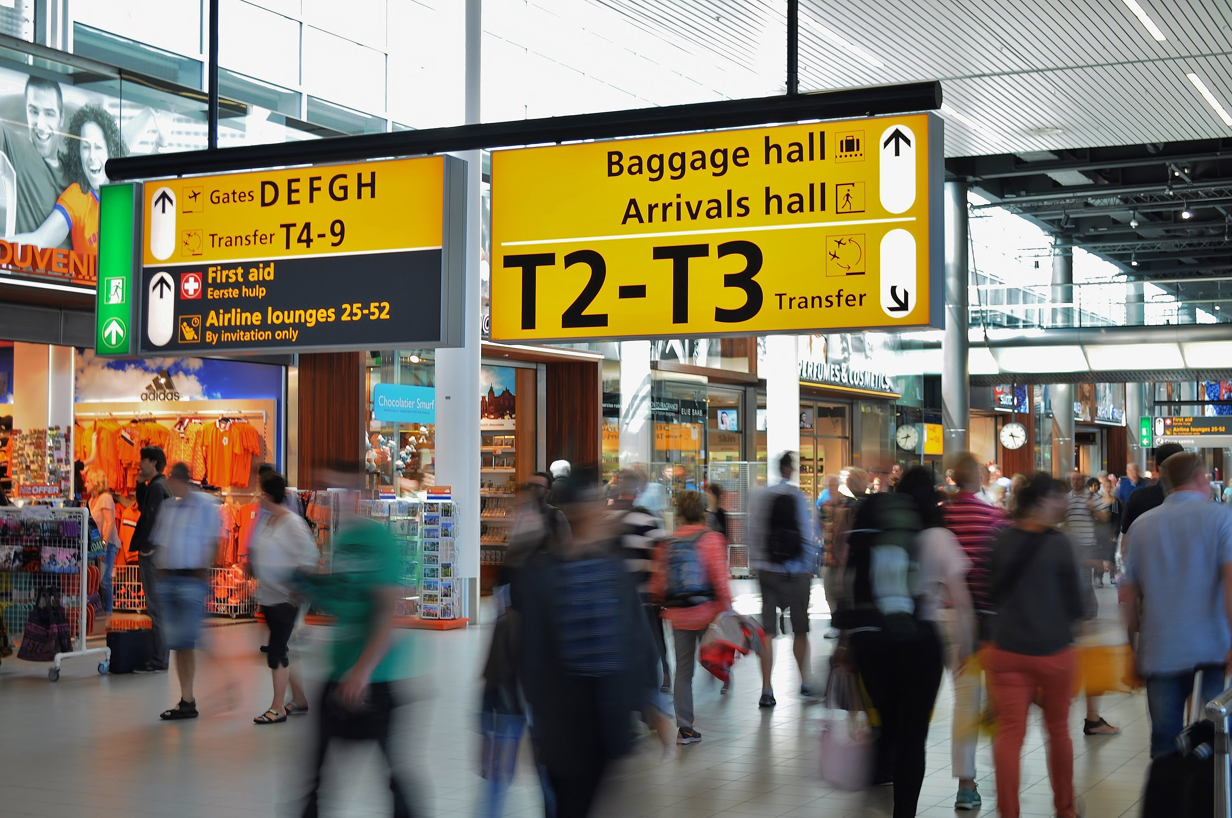 People Walking Beside Baggage Hall and Arrivals Hall Signage