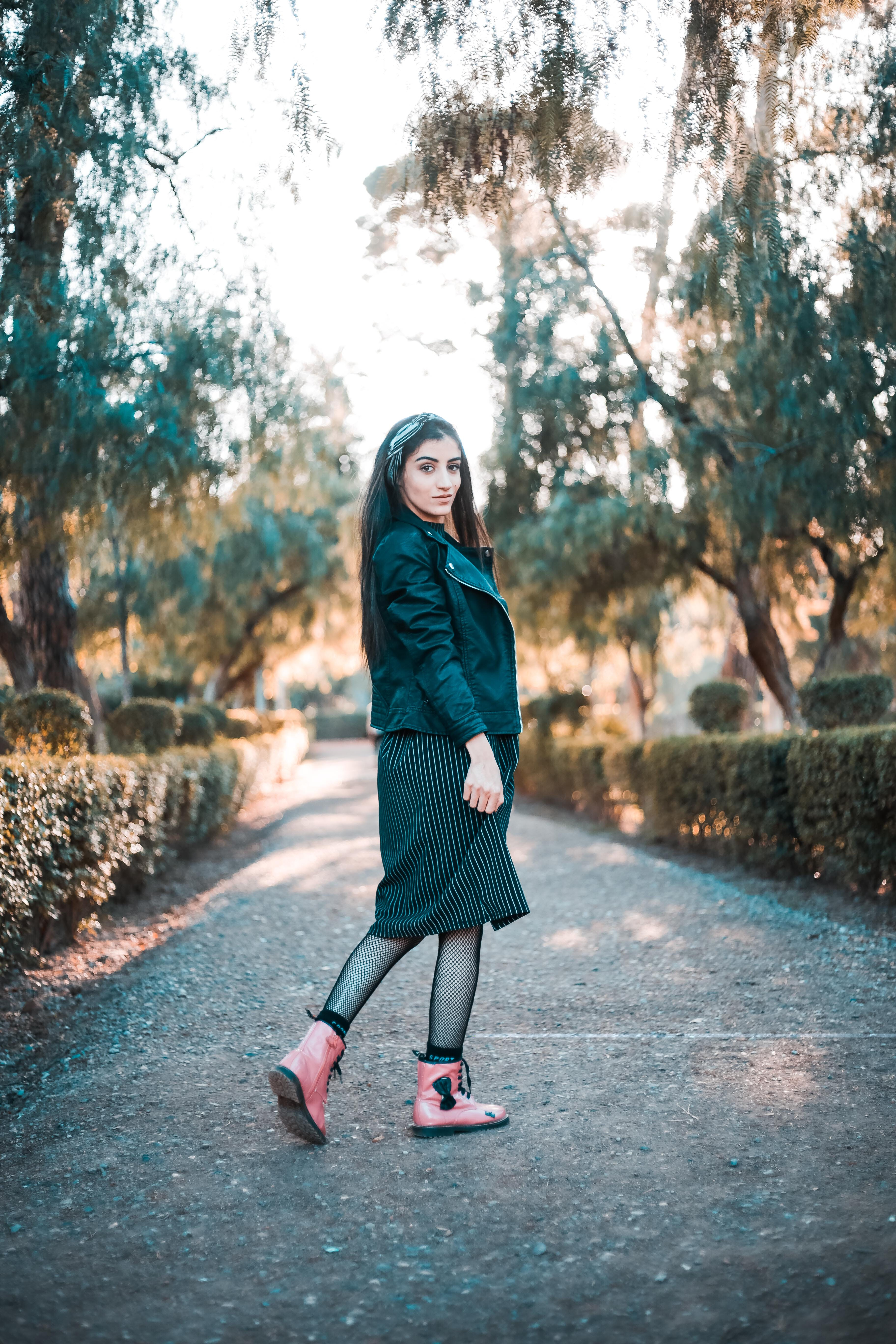 Woman in Black Jacket, Skirt, and Pink Boots