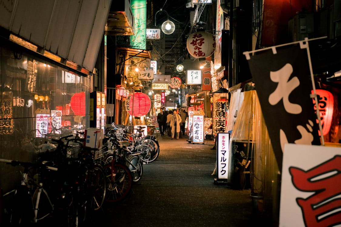 Bicycles Parked Near Japanese Store during Night Time