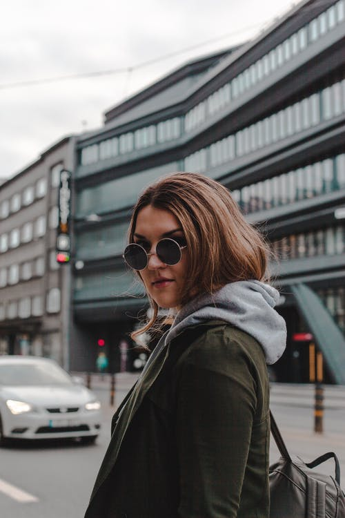 Woman Leaning Backward Wearing Sunglasses and Coat
