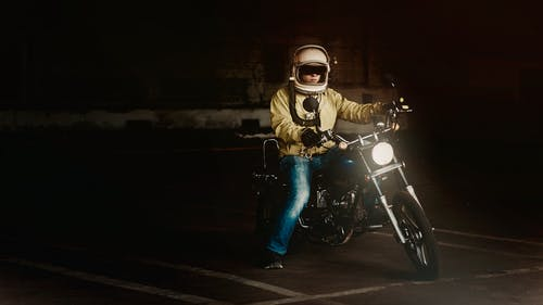 Man Wearing White Full Face Helmet Riding on Standard Motorcycle