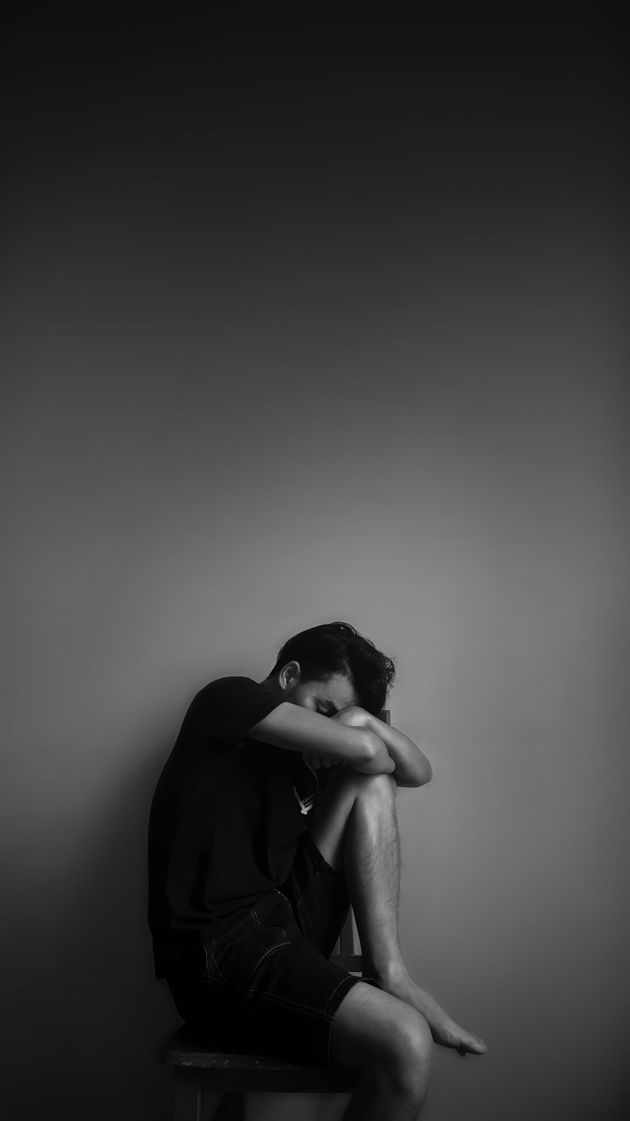 Grayscale Photography of Man Sitting Beside Wall