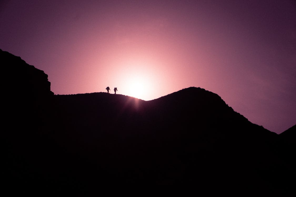 Silhouette Photo of Two Persons Standing on Black Mountain Peak