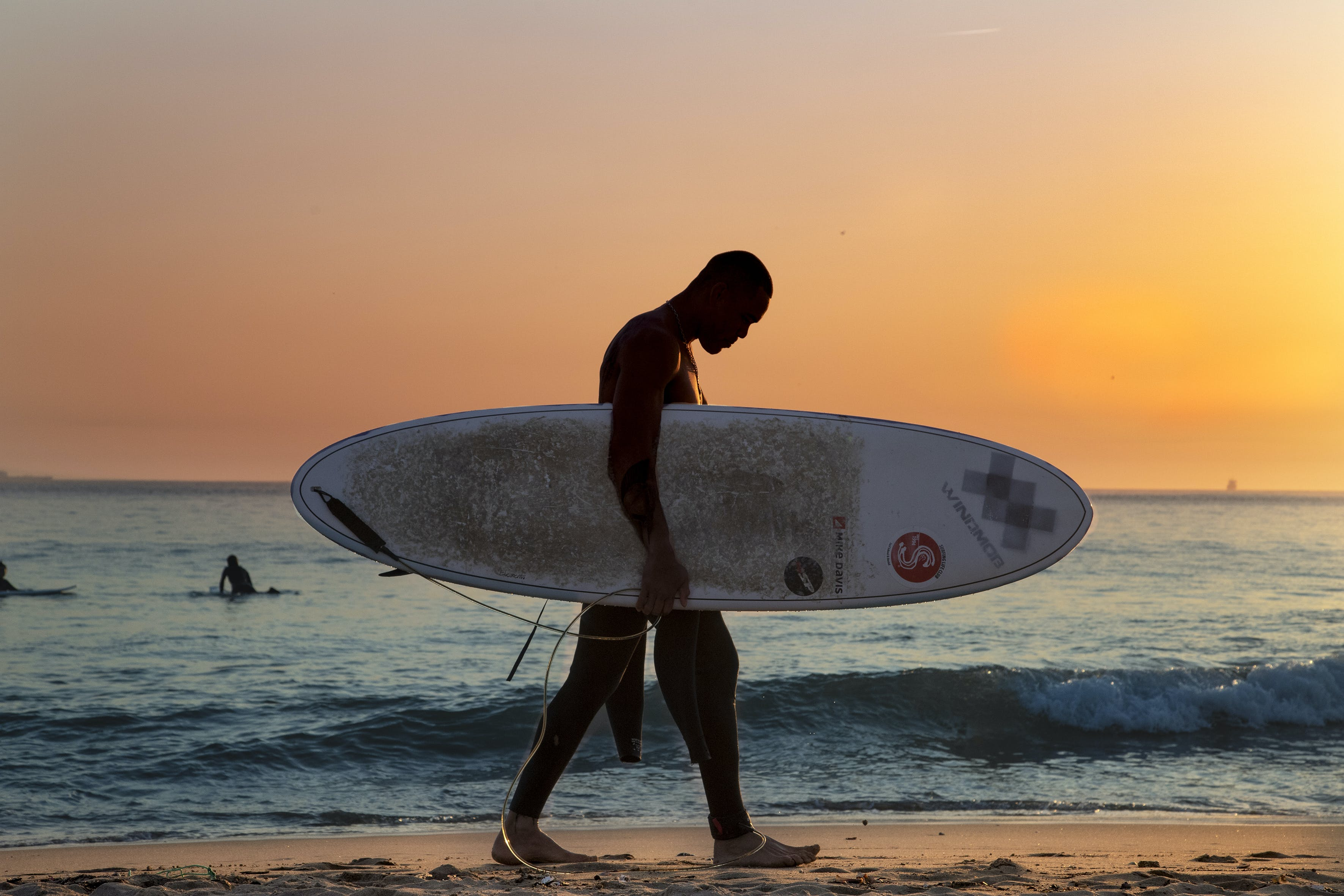 Man Carrying White Surfboard on Beach