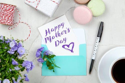 Glückliche Muttertagskarte Neben Stift, Makronen, Blumen Und Schachtel Nahe Kaffeetasse Mit Untertasse