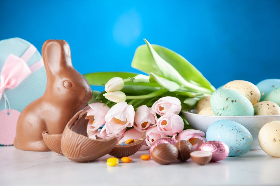 White flowers between brown rabbit figure and eggs