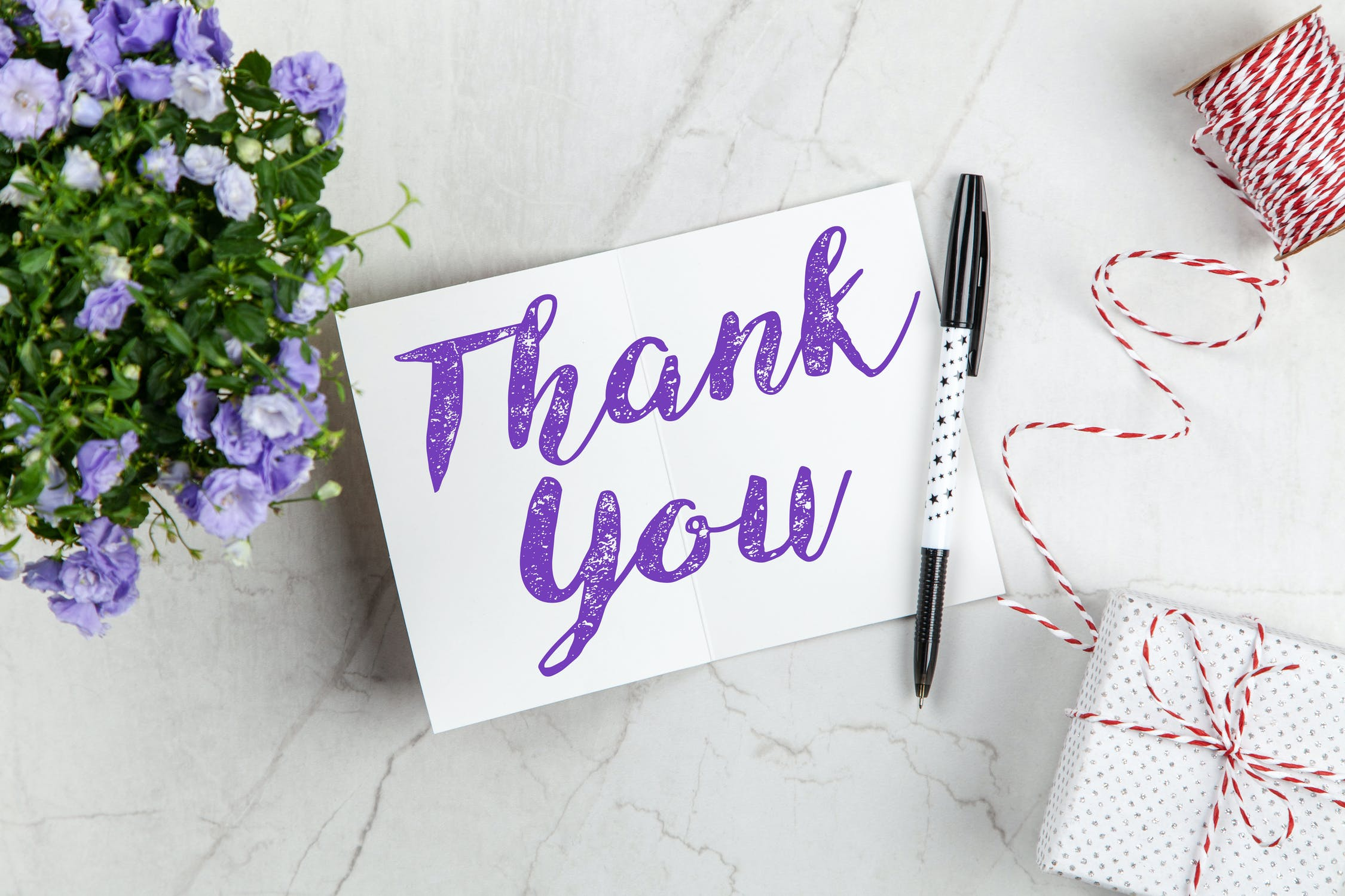An open thank you note on a table reading 'Thank you!' in purple opulent script. Photo by pexels user Giftpundits.com. Photo used courtesy of pexels.com.