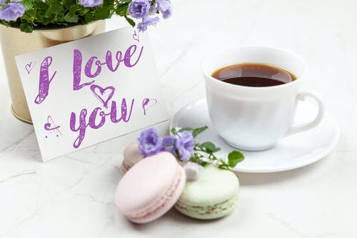 White Ceramic Teacup on Saucer next to Love Message