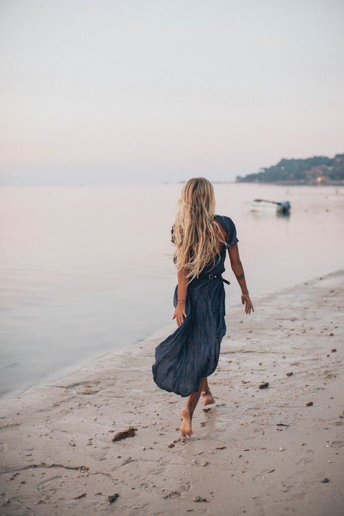 Photo of Woman Walking On Seashore