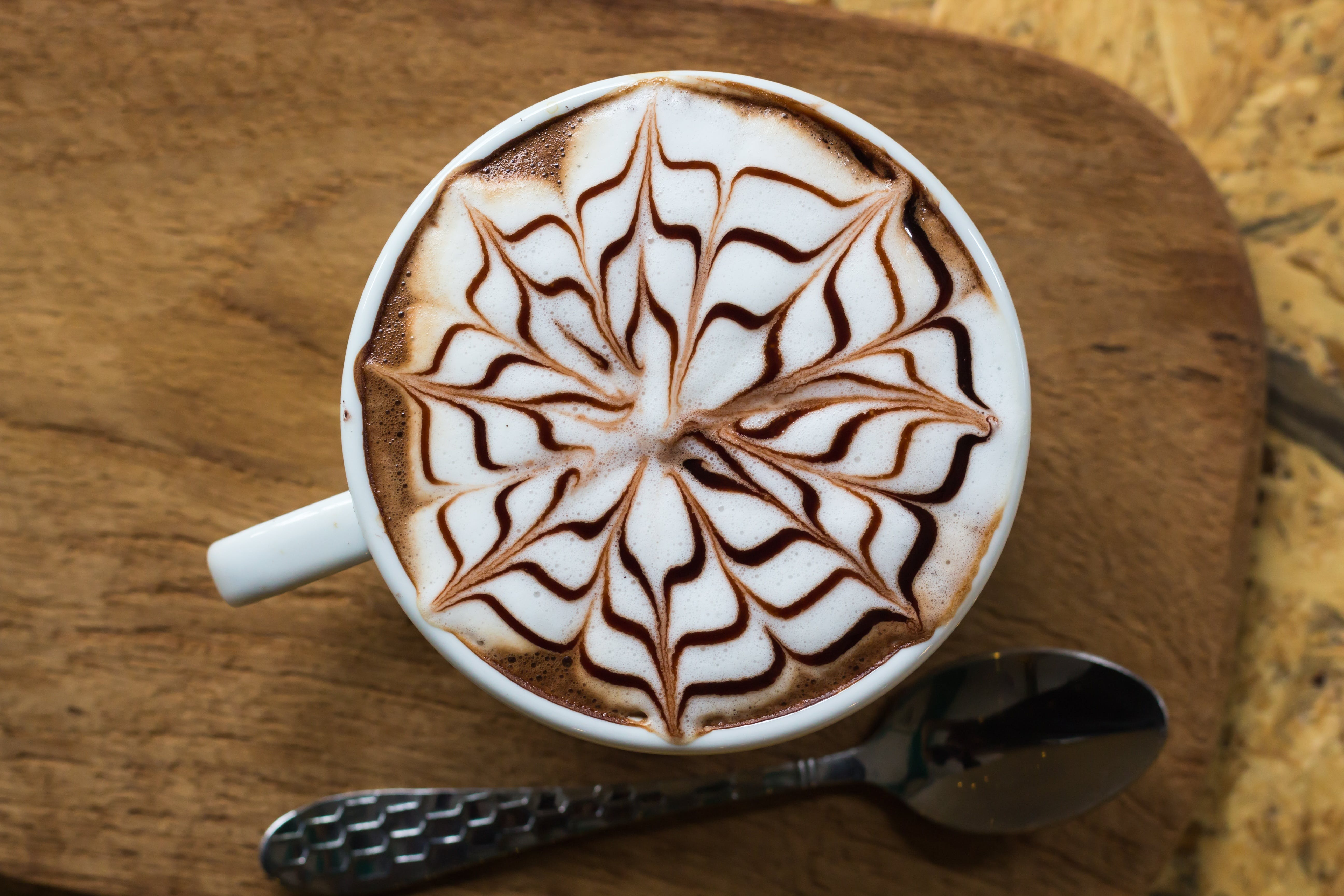 Brown and White Coffee With Floral Art in White Ceramic Mug