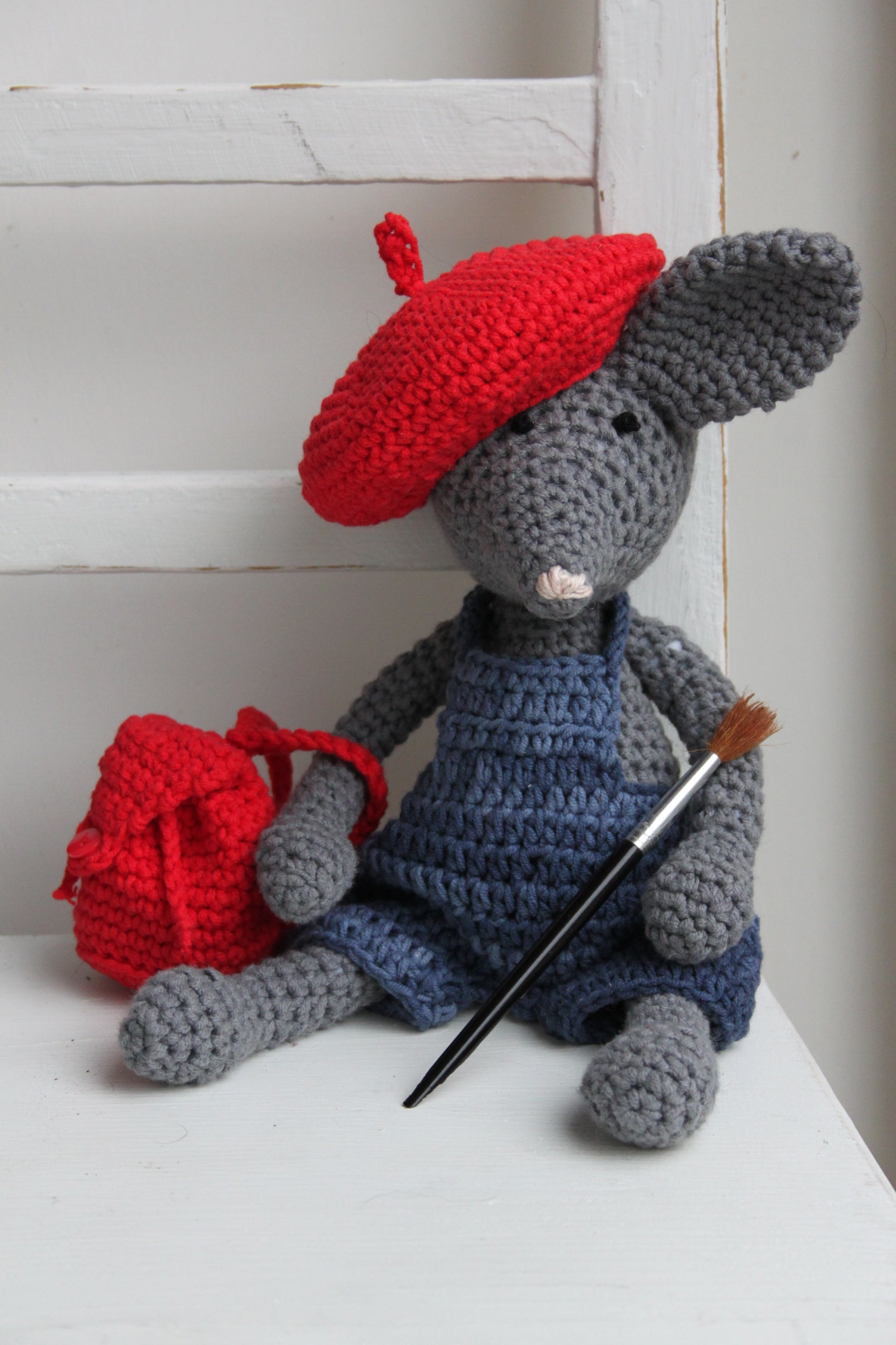 Gray Crochet Mouse With Red Backpack Plush Toy on White Surface