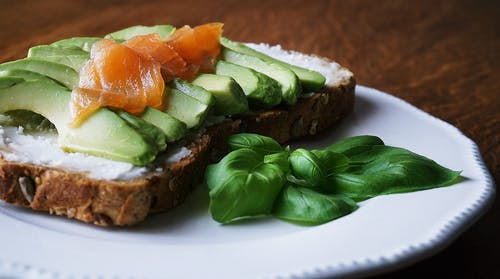 Bread With Sliced Avocado and Salmon Near Basil Mint on Plate