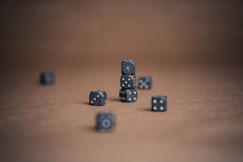 Black and Silver Dice on Brown Wooden Table