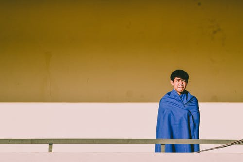 Man Covered With Blue Blanket Standing Near Gray Handrail